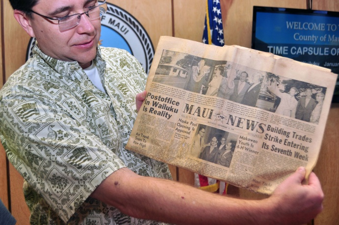 MD Keith Regan holding one of the items that was placed in the time capsule, a Maui News dated Sept. 19, 1959.
