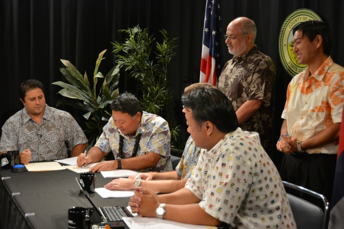 Mayor Arakawa signing the agreement at the Akakū studio in Kahului. Seated from left to right: Communication Director Rod Antone, Mayor Alan Arakawa, Managing Director Keith Regan (hidden), Chief of Staff Herman Andaya. Standing in the back observing are Anaergia Director of Business Development Karl Bossert and Maui County Department of Environmental Management Director Kyle Ginoza.