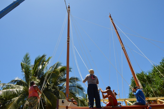 38 foot Mast are hoisted aboard Moʻokiha o Piʻilani and crew members seat the masts and tie down the stays. This is the last milestone before the canoe moves to Mala Wharf for a July 11 public launch. Photo by Aimee Paradise.