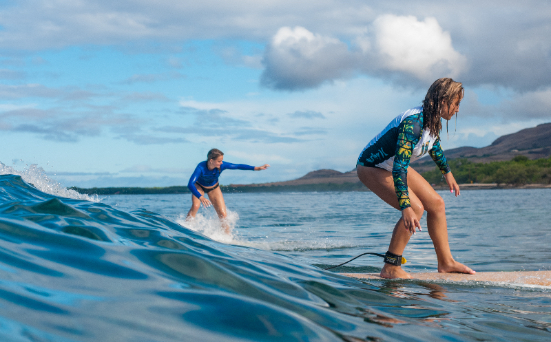 Maui Surfer Girls teen campers Allie and Lexi ride a party wave. Photo courtesy Lauren Stirpe.