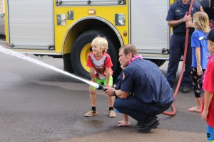 Trucker Dukes shooting water with his dad, firefighter Joshua Dukes and his brother outside of the Kahului Fire Station. Photo by Wendy Osher.