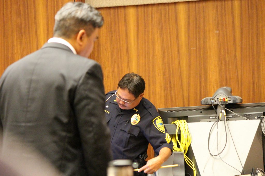 Sgt. Wendell Loo pointing to a photo of injury marks on on the defendant's hands (6.29.16) Photo by Wendy Osher.