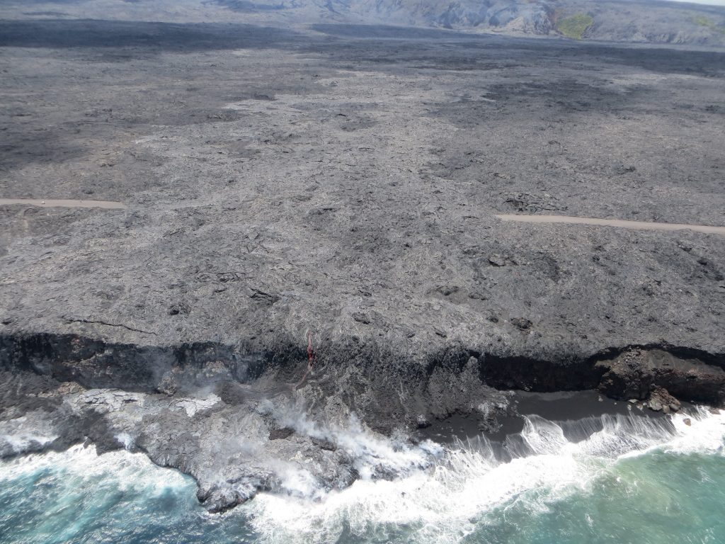 """During today's overflight of Kīlauea Volcano's """"61g"""" lava flow, the ocean entry appeared less robust, with only one small flow of active lava streaming over the sea cliff. The second, smaller ocean entry point, west of this main entry (noted in our July 29 photo), was not active at the time of the overflight. (8.2.16) Photo credit: HVO/USGS."""