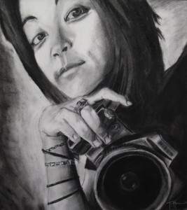 Second Place: Tanner Morrin, H.P. Baldwin High School, 12th grade Title: Tiny Inspiration (Woman holding Nikon Camera) Medium: Charcoal