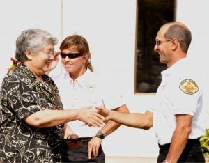 Photo courtesy: County of Maui.  Lifeguard graduate Joao Batista is congratulated by Mayor Charmaine Tavares while County Chief of Aquatics Mary Kielty looks on.