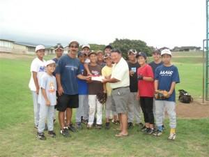 (Former Mayor Alan Arakawa presents a check to the Central East Maui Little League coach, Glenn Yonashiro on Wednesday.  Courtesy Photo.)