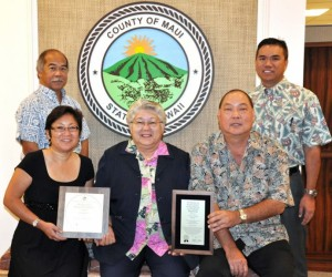 Photo Courtesy: County of Maui. L-R: Budget Director Fred Pablo (standing); Helene Kau, Assistant Budget Director; Mayor Charmaine Tavares; Ty Yoshimi, Accounting System Administrator; Kalbert Young, Finance Director (standing).