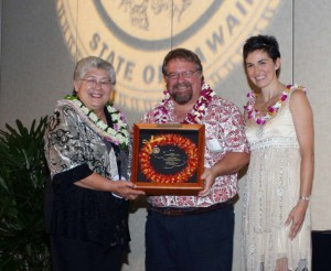 David Fisher (center) receives the Mayor's Community Service Award from Mayor Charmaine Tavares (L) and Economic Development Coordinator Deidre Tegarden (R). Fisher is among the instructors scheduled to speak during the January County of Maui Brown Bags workshops.  Photo by: Sheryl Saphore Photography.