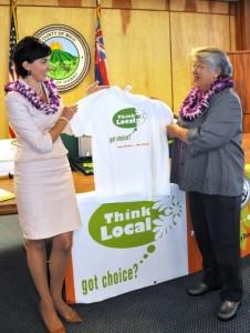 Mayor Charmaine Tavares looks at a promotional t-shirt displayed by Economic Development Coordinator Deidre Tegarden (left).