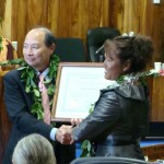 County Clerk Jeffrey Kuwada presents West Maui Councilmember Elle Cochran with her certificate of office. Photo by Wendy Osher.