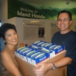 Anne Oishi, vice-president and general manager of Island Honda, presents prepaid cell phones and phone cards to Keith Regan, co-founder of The Aloha Initiative.