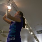 Pacific Whale Foundation employee Tara McBarnett replaces an old halogen bulbs with a new energy efficient LED light bulbs at Pacific Whael Foundation's Ocean Store in Ma'alaea.