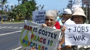 An estimated 25 to 30 people showed up for a sign waving rally fronting the Old Kahului Shopping Center on Maui Sunday afternoon.  Photo by Wendy Osher.