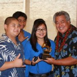 George Kahumoku, flanked by his students, receiving a Grammy Award. Photo courtesy of UHMC.