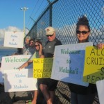 Signs in support of a Molokai cruise operation were waved from shore, as protesters opposed to the operation took to the water in a small blockade on Saturday. Courtesy photo.
