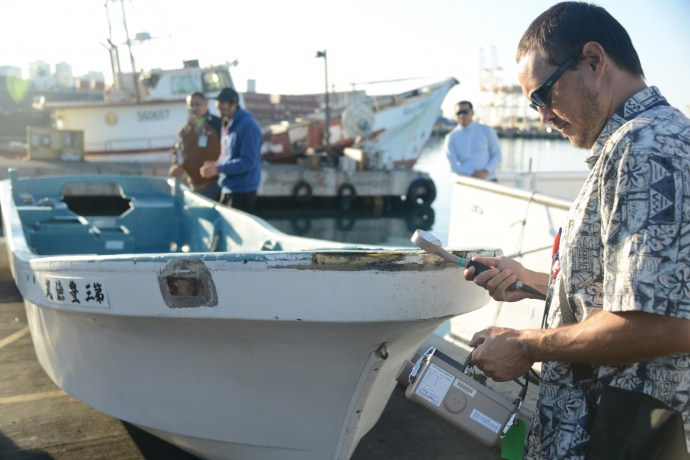 Joshua Marvit, State of Hawaii Dept. of Health, tests a 16 foot skiff for radiation after the vessel was salvaged by the crew of the F/V Zephyr approximately 800 miles north of Honolulu, Oct. 5, 2012. The skiff was confirmed to have been debris from the 2011 Japan Tsunami by the Japanese Consulate, after they contacted the owners through the Japanese Ministry of Foreign Affairs, and confirmed that they did not seek its return. The Department of Land and Natural Resources and the State of Hawaii Department of Health conducted radiation tests and a search for invasive species as a precautionary measure. U.S. Coast Guard photo by Petty Officer 2nd Class Eric J. Chandler.