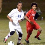 Baldwin High School's Kailoa Akoi (24) maintains possession as Lahainaluna's Keoni Miranda (4) defends. Akoi scored the Bears' second goal of the match Friday in the 18th minute as Baldwin defeated Lahainaluna 2-1 at Keopuolani Park. Photo by Rodney S. Yap.