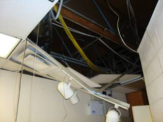 Damage to ceiling panel, lighting, and wiring of the prisoner processing room.  Courtesy photo.