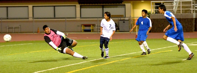 Kamehameha Maui's Daniel Quenga (7) scores the first of his two goals Tuesday night against Maui High. Saber goalkeeper Pani Kapisi stretches out to try and deflect Quenga's shot attempt. Photo by Rodney S. Yap.