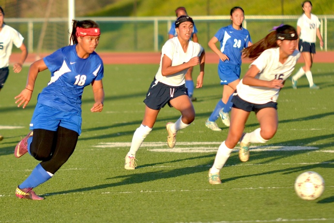 Maui High junior Mary-Lynn Johannes (18) starts the breakaway that led to her shot attempt just above the crossbar in the closing seconds of the first half. Kamehameha Maui's Kailin Barcoma (4) and Raven Neizman (4) hurry to get back on defense. Photo by Rodney S. Yap.