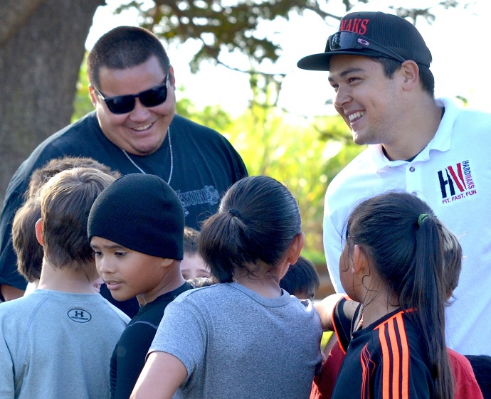 Cody Nakamura (right) and Kai Maiava (left) share a laugh with the grade-school campers Saturday following their one-hour session at Maui Tropical Plantation field. Photo by Rodney S. Yap.