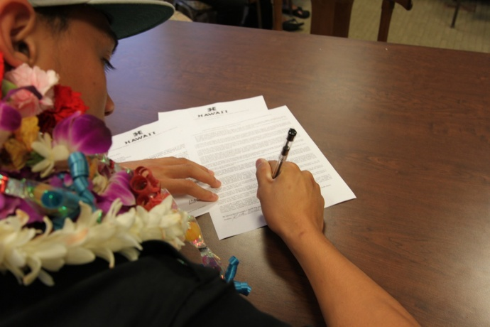 Baldwin's Keelan Ewaliko puts the pen to the paper Wednesday, signing his letter of intent to play football for Hawaii. Photo by Ben Juan.