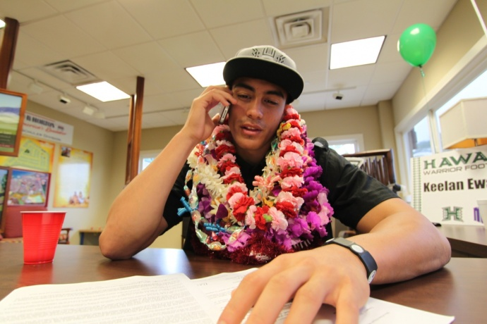 Baldwin's Keelan Ewaliko talks to Hawaii coach Norm Chow after signing his letter of intent to play with the Warriors on Wednesday. Photo by Ben Juan.