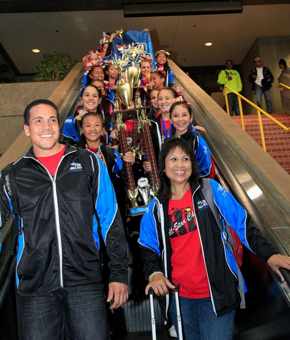 Hawaii All-Star Cheerleaders head coach Kealii Molina (left) and assistant coach Jo-Ann Yap lead the championship parade down the escalator the Kahului Airport baggage claim Monday, March 25. Photo by Ben Juan.
