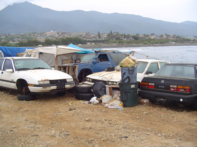 Homeless parked at Kahului Harbor on Maui.  File photo by Wendy Osher, March 2006. The camp was cleared during a subsequent sweep of the area.  Several tent shelters have gone up since then along the shoreline of the harbor in the naupaka bushes.