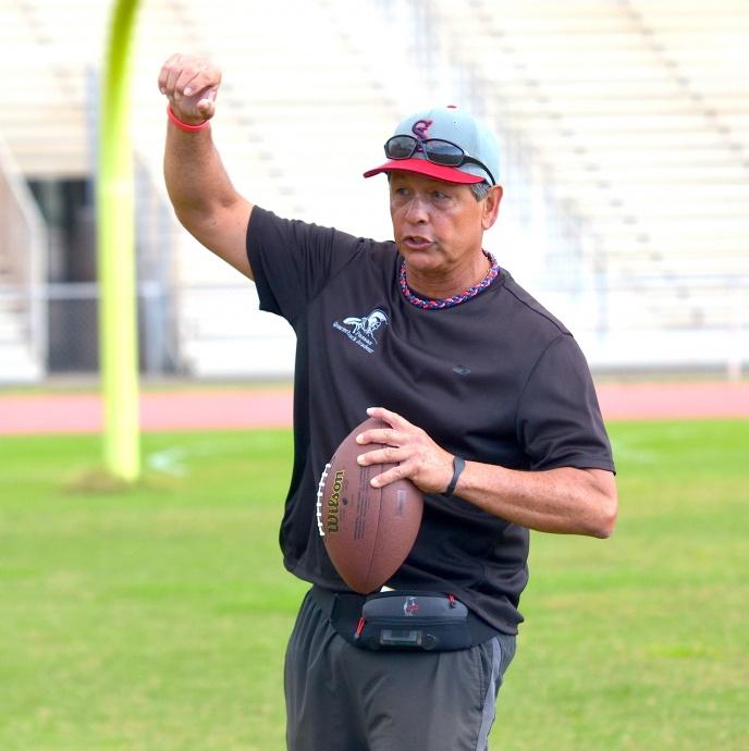 Saint Louis School coach Vince Passas explains the proper release to a group of quarterbacks Saturday at War Memorial Stadium. Photo by Rodney S. Yap.