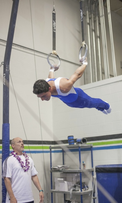 Valley Isle Gymnastics' Daniel Kapua holds the static-lever position on rings as his coach Rusty Gage looks on. Photo by Valley Isle Gymnastics.