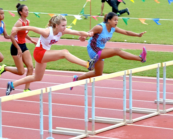 Seabury Hall's Christy Fell battles Baldwin's Raeana Anguay in the girls 100 hurdles Saturday. Fell won a close race in a time of 16.14 seconds to Anguay's 16.15. Photo by Rodney S. Yap.
