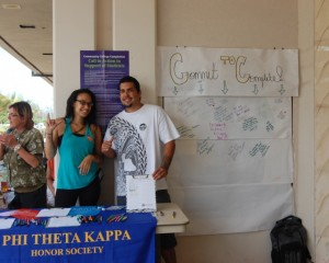 Photo by UHMC student HeatherLyn Gray. Description: UHMC Phi Theta Kappa members Corey Kanae and Megan Simmons gathering signatures for Pledge to Complete