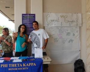Photo by UHMC student HeatherLyn Gray. Description: UHMC Phi Theta Kappa members Corey Kanae and Megan Simmons gathering signatures for Pledge to Complete