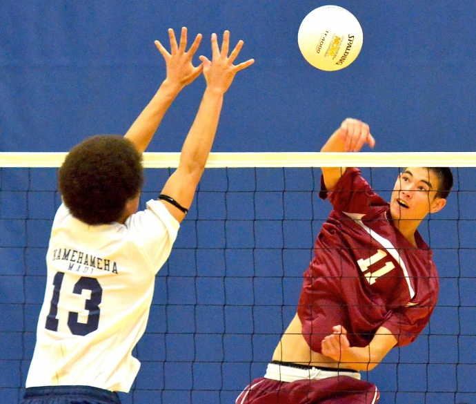 Baldwin High Schol's Trent Helle (11) hits past the block of Kamehameha Maui's Kahiau Andrade (13) in Tuesday's MIL boys volleyball action at the Warriors' gym. Photo by Rodney S. Yap.