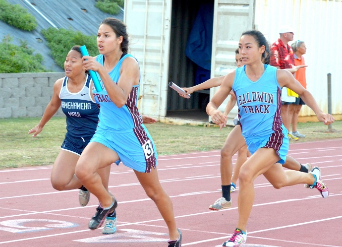 Baldwin High's Thyna Guedes takes the baton from teammate Amber Kozaki en route to winning the 4x100 relay. Photo by Rodney S. Yap.