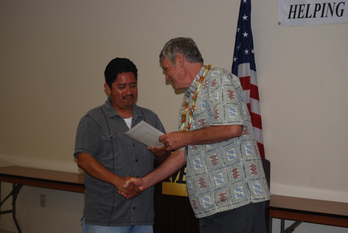 Graduate Jose Castellanos receives a certificate of achievement from Craig Swift, the director of the Maui Economic Opportunity's Business Development Center. Courtesy photo.