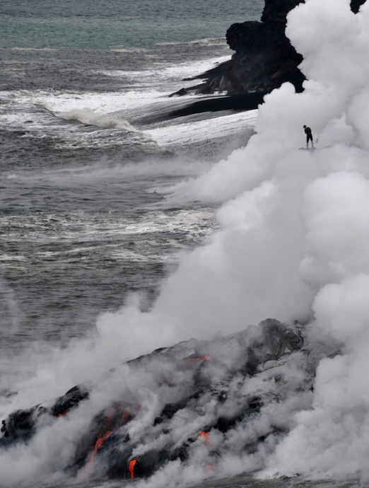 Do not be misguided by the risky actions of this person (upper right), who is standing on an active lava delta that could collapse without warning, amidst a plume of superheated steam, hydrochloric acid, and tiny particles of volcanic glass.  To avoid these ocean entry hazards, HVO advises staying at least 400 m (one-quarter mile) from where lava enters the sea. Photo courtesy Hawaiian Volcano Observatory.