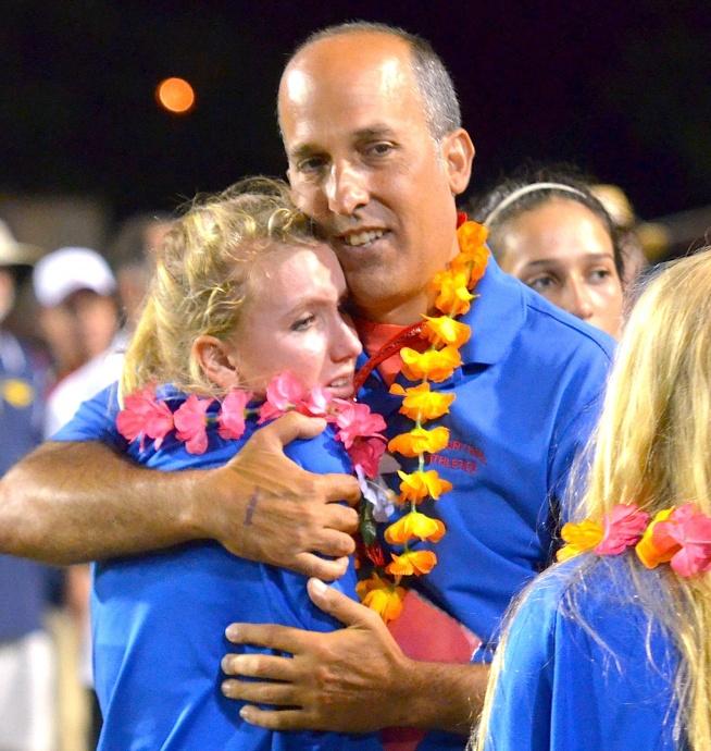 Seabury Hall head coach Bobby Grossman hugs hurdler Christy Fell after the meet Saturday. Photo by Rodney S. Yap.