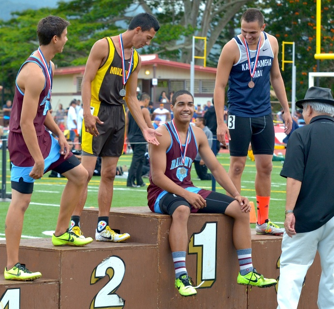 Baldwin high hurdler champion Abraham Reinhardt sits on the awards stand after receiving his gold medal. Teammate Tyler Feiteira (left) and Connor Yap of Kamehameha Maui (right) offer to assist Reinhardt to his feet for picture taking. Photo by Rodney S. Yap.