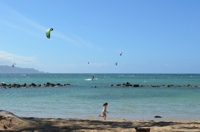 A kite surfer appears to be heading for the break in the rockwall at Ka'a Point, as children play nearby. Photo courtesy of Philip Botek.