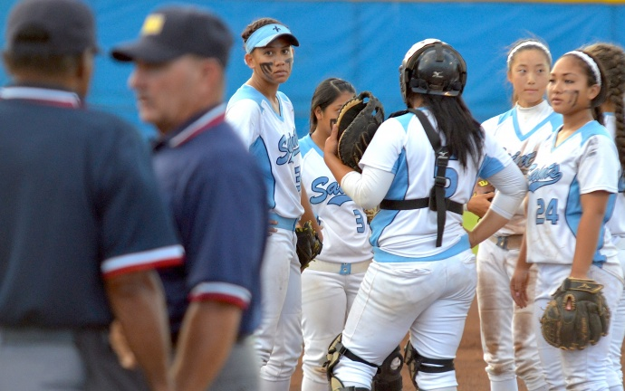 Saint Francis players wait while umpires discuss a ruling Friday at the girls Division II state softball tournament. Photo by Rodney S. Yap.