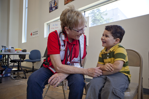"Nicolas Zipperer, 4, shows nurse Sharon Gettman, an American Red Cross volunteer, his ""owie,"" covered in a bandage. Nurse Gettman counsels the young Peeples Valley resident through his pain, assuring him that his ""owie,"" like the wildfire conditions, will feel better in time. She offers medical attention to any affected people in need at the local Red Cross shelter in Prescott, Arizona.   Tuesday, July 3, 2013, Prescott, Arizona. At the local Red Cross shelter in Prescott, Arizona Photos by Talia Frenkel."