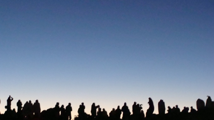Haleakalā Visitor Center. Silhouettes of sunrise watchers line the horizon.  People Pōhaku, photo by Wendy Osher.