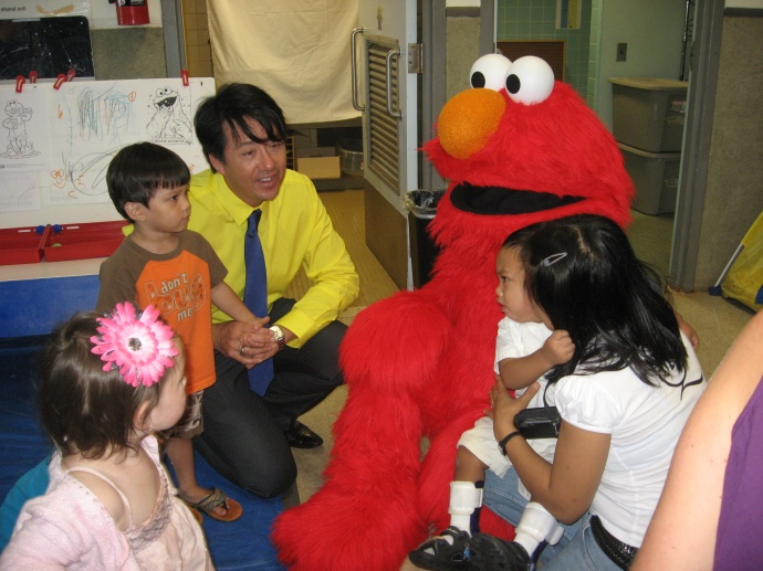 Executive Director Dean Wong and some clients visit with Elmo. Courtesy photo