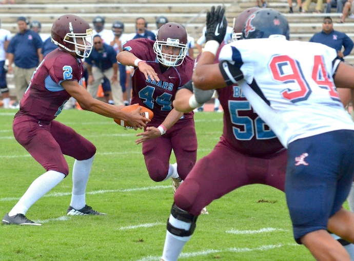 Baldwin High School running back Dusty Flores takes a handoff from quarterback Jonovan-Tage Akaka Foster as veteran lineman Alexander Ezera (52) tries to slow down Saint Louis lineman Peter Sagapolutele (94) during first-quarter action Saturday at War Memorial Stadium. The Crusaders defeated the Bears 55-0. Photo by Rodney S. Yap.