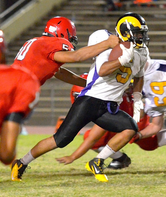 Lahainaluna's Hercules Mata'afa gets a paw on Mt. Douglas running back Marcus Davis. Photo by Rodney S. Yap.