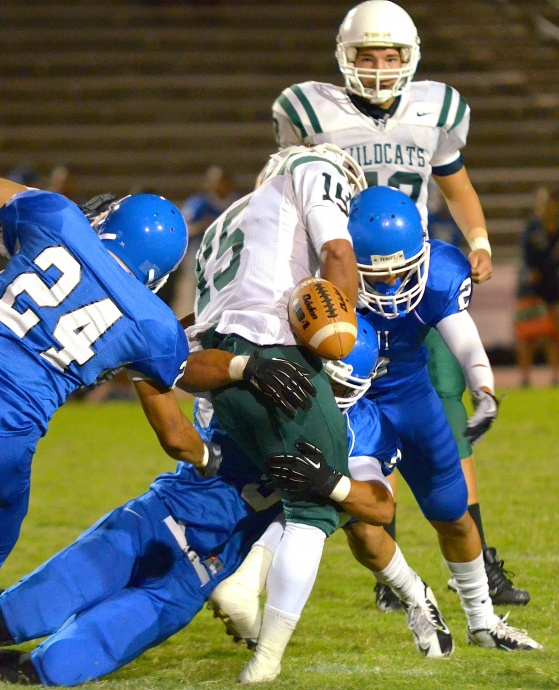 Maui High's Andre Pierman forces the ball lose on this tackle. Photo by Rodney S. Yap.