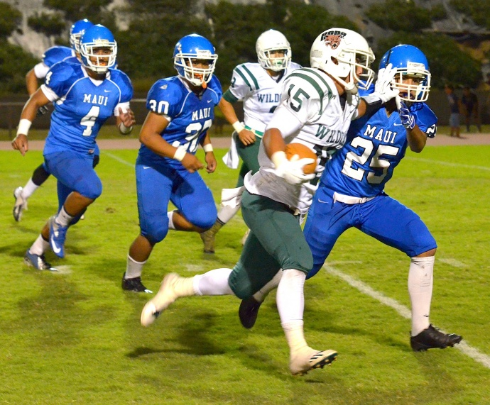 Maui High's Justin Carvalho takes a stiff arm to the face as he tries to tackle Konawaena's Chase Takaki Saturday at War Memorial Stadium. Photo by Rodney S. Yap.