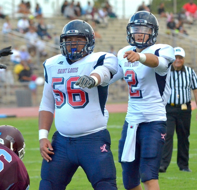 St. louis quarterback Ryder Kuhns (2) and center C.J. Leleo (56) call out the Baldwin defensive alignment during second-quarter action Saturday at War Memorial Stadium. St. Louis rolled over Baldwin 55-0. Kuhns finished with three touchdown passes and completed 9 of 1o pass attempts for 206 yards. Photo by Rodney S. Yap.